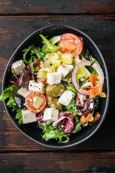 Griechischer salat, auf altem dunklem holztisch, draufsicht flach gelegt