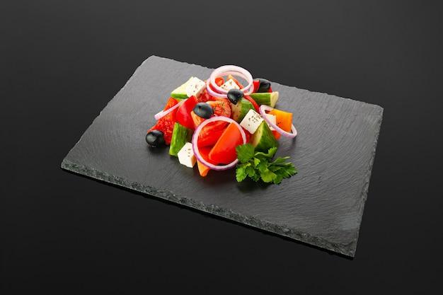 Griechischer salat auf einem schwarzen schieferbrett