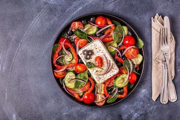 Griechischer salat auf einem schwarzen teller