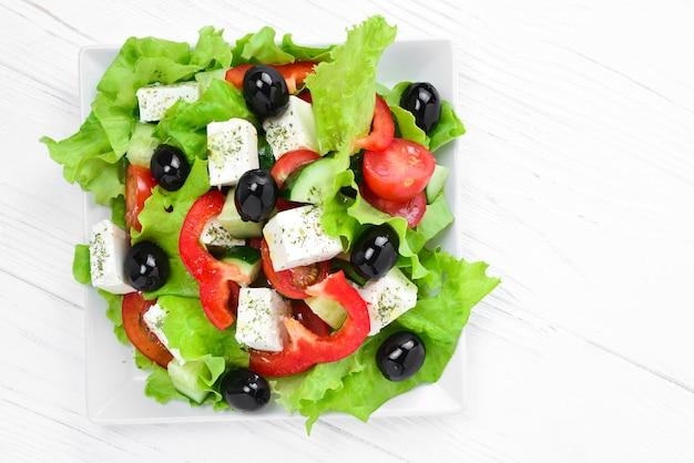Griechischer salat auf einem weißen hölzernen hintergrund. platz für text oder design.