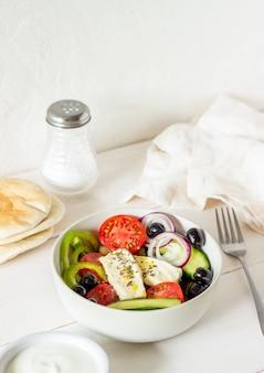 Griechischer salat auf einem weißen holz