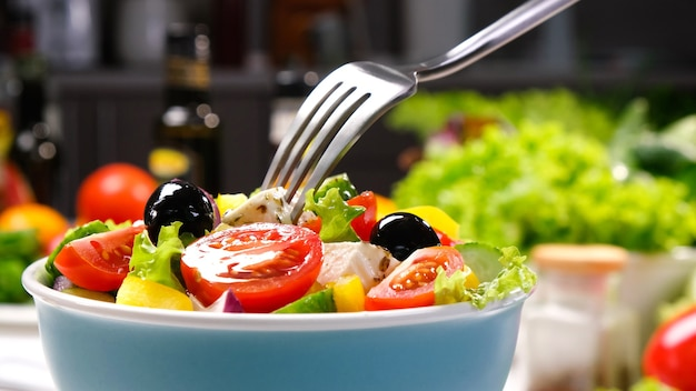 Griechischer salat auf gabel mit feta-käse und oliven, frischer gemüsesalat mit gesunden zutaten, mediterrane küche