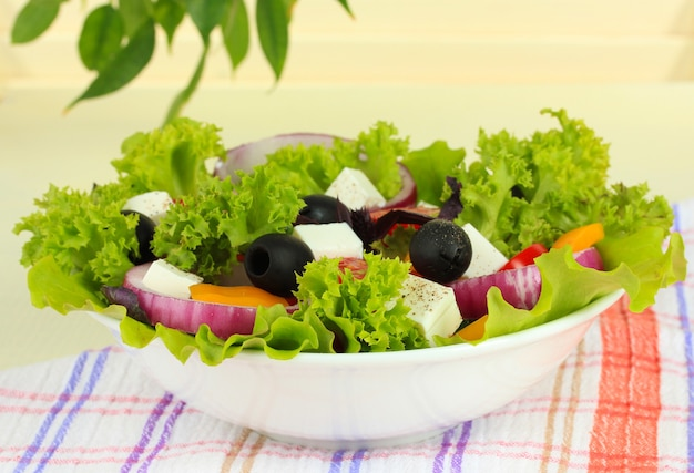Griechischer salat auf teller auf dem tisch auf hellem hintergrund