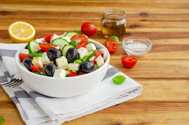 Griechischer salat aus frischem saftigem gemüse, feta-käse, kräutern und oliven. gesundes essen.