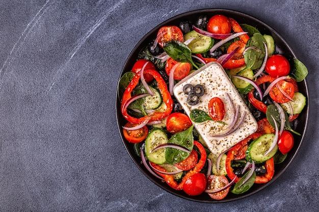 Griechischer salat aus frischer gurke, tomate, paprika, roten zwiebeln, feta-käse und oliven