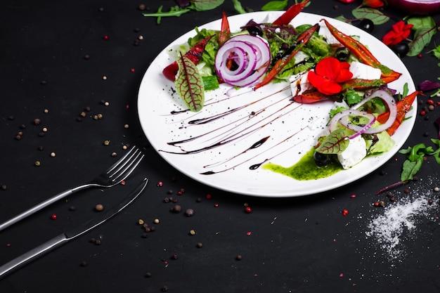Griechischer salat aus frischer gurke, tomate, paprika, salat, roten zwiebeln, feta-käse und oliven mit olivenöl.