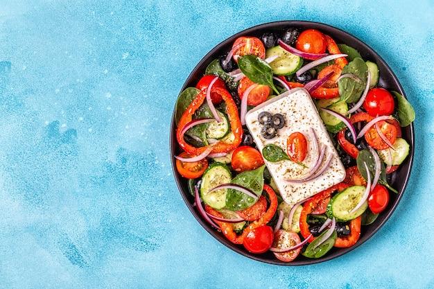 Griechischer salat aus frischer gurke, tomate, paprika, spinat, roten zwiebeln, feta-käse und oliven