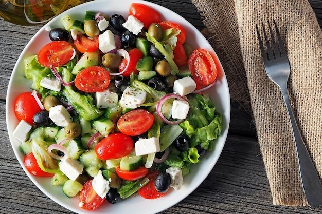 Griechischer salat aus rohem gemüse, gewürzt mit olivenölsalz und oregano