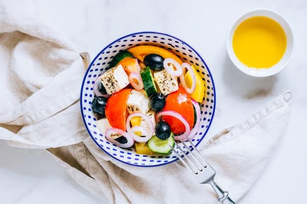 Griechischer salat der draufsicht mit olivenöl auf marmor.