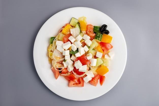 Griechischer salat des gesunden essens auf einer grauen oberflächenoberansicht.