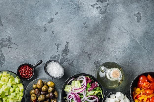 Griechischer salat hauptzutaten frische oliven mischen, feta-käse, tomaten, pfeffer, auf grauem tisch, draufsicht flach legen