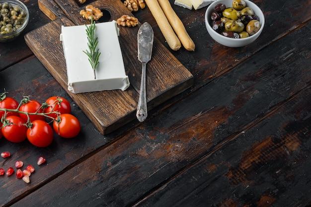 Griechischer salat hauptzutaten, frische olivenmischung, feta-käse, tomaten, auf dunklem holztisch