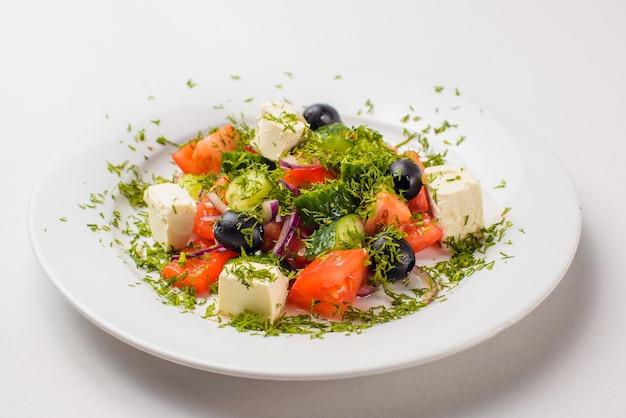 Griechischer salat in einem teller auf einem weißen