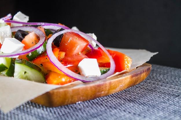 Griechischer salat in einer hölzernen platte