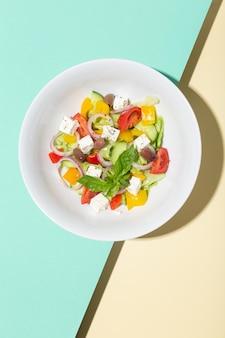 Griechischer salat in weißen platten mit harten schatten auf blauem und gelbem foto von hoher qualität