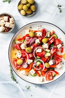 Griechischer salat mit feta-käse, tomaten, rotem pfeffer, oliven und gurken