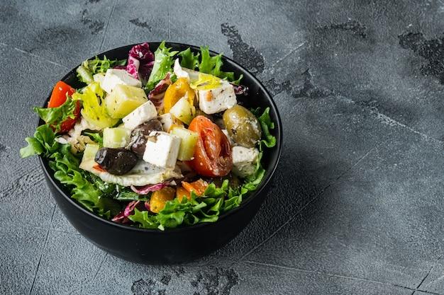 Griechischer salat mit feta-käse und frischen bio-oliven, auf grauem tisch mit platz zum kopieren