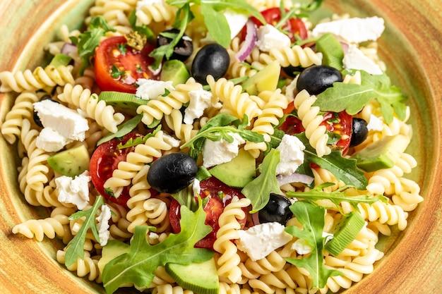 Griechischer salat mit frischem gemüse, feta-käse, nudeln und schwarzen oliven. mediterrane küche. hintergrund für lebensmittelrezepte. nahansicht.