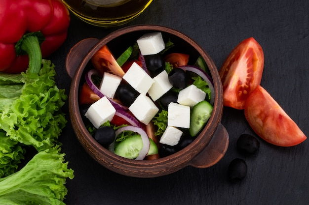Griechischer salat mit frischem gemüse, feta-käse und schwarzen oliven auf dunklem hintergrund. ansicht von oben. .
