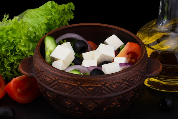 Griechischer salat mit frischem gemüse, feta-käse und schwarzen oliven auf dunklem hintergrund.