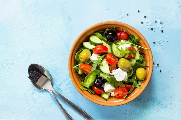 Griechischer salat mit frischem gemüse, feta-käse und schwarzen oliven auf einem blauen stein- oder betontisch