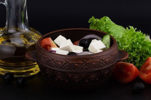 Griechischer salat mit frischem gemüse, feta-käse und schwarzen oliven auf einem dunklen hintergrund.