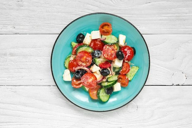 Griechischer salat mit frischem gemüse, feta-käse und schwarzen oliven in einem teller auf weißem holztisch