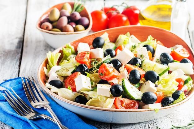 Griechischer salat mit frischem gemüse, feta-käse und schwarzen oliven Premium Fotos