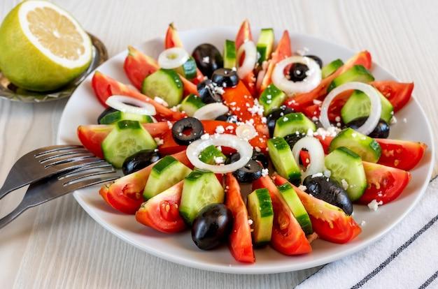 Griechischer salat mit frischem gemüse, feta und schwarzen oliven auf dem tisch