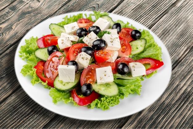 Griechischer salat mit frischem gemüse im hintergrund