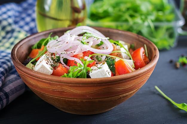 Griechischer salat mit frischen tomaten, gurken, roten zwiebeln, basilikum, feta, schwarzen oliven und italienischen kräutern