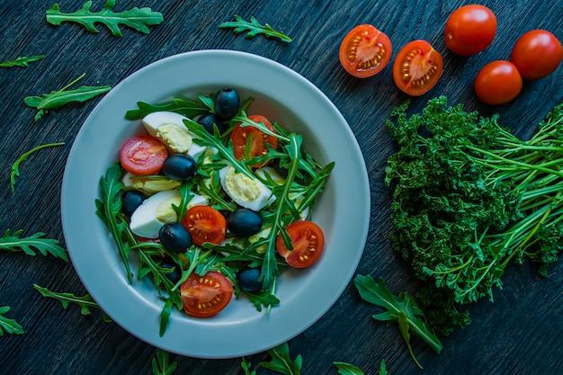 Griechischer salat mit frischen tomaten, rucola, eiern und oliven