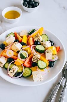 Griechischer salat mit olivenöl auf marmor.
