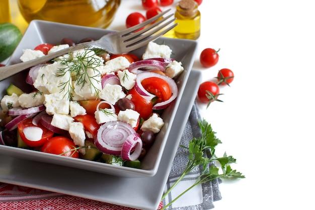 Griechischer salat mit tomaten, feta, gurken, zwiebeln und oliven