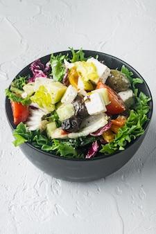 Griechischer salat mit tomaten, pfeffer, oliven und feta auf weiß
