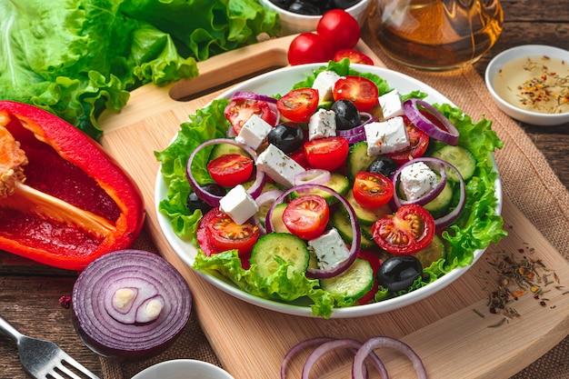 Griechischer salat nahaufnahme auf einem braunen hintergrund mit zutaten. seitenansicht. kochkonzept.