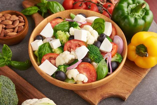 Griechischer salat oder horiatiki mit großen stücken von tomaten, gurken, zwiebeln, feta-käse und oliven in der weißen schüssel isolierte draufsicht. dorfsalat mit gewürfeltem mozzarella, rucola, petersilie und olivenöl