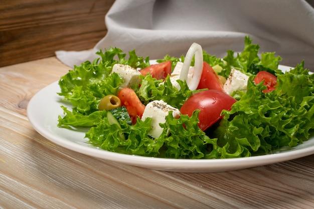 Griechischer salat oder horiatiki mit großen stücken von tomaten, gurken, zwiebeln, feta-käse und oliven in weißer schüssel nahaufnahme. grüner dorfsalat mit mozzarellawürfeln, salat, gewürzen und olivenöl