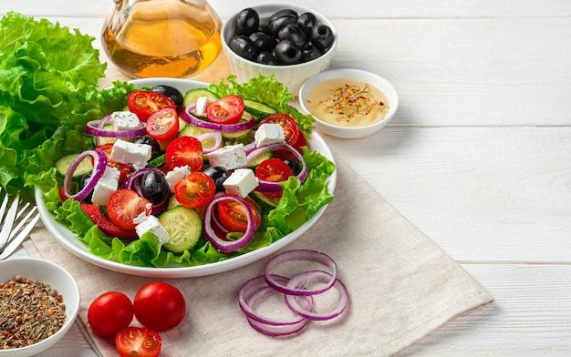 Griechischer salat und frische zutaten auf einem weißen hölzernen hintergrund. seitenansicht mit kopierraum.