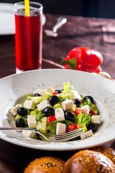 Griechischer salat von der seitenansicht mit brot und pilzen der schwarzen oliven