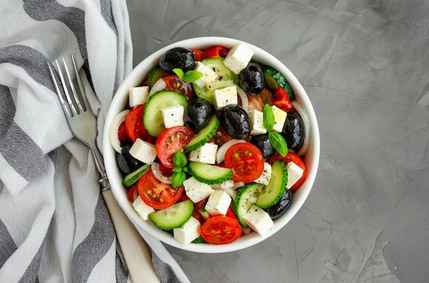 Griechischer salat von frischem saftigem gemüse, feta-käse, kräutern und oliven in einer weißen schüssel auf einem dunklen betonhintergrund. gesundes essen. horizontale ausrichtung. draufsicht.