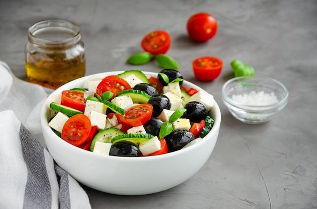 Griechischer salat von frischem saftigem gemüse, feta-käse, kräutern und oliven in einer weißen schüssel auf einem dunklen betonhintergrund. gesundes essen.
