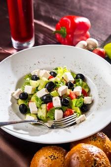 Griechischer salat von oben mit schwarzem olivenbrot und pilzen