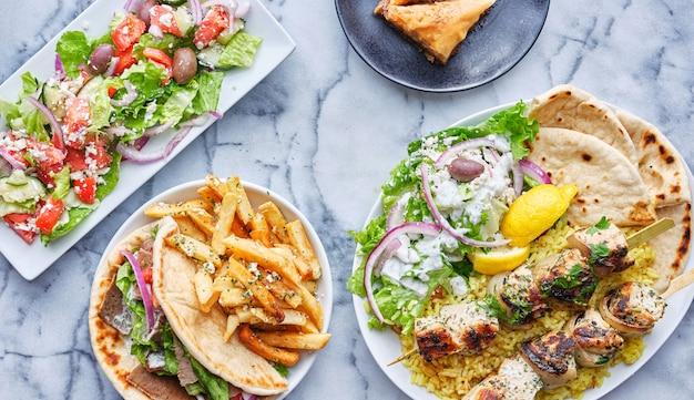 Griechisches essen mit hühnchen-souvlaki-platte, gryos, pommes frites, salat und baklava