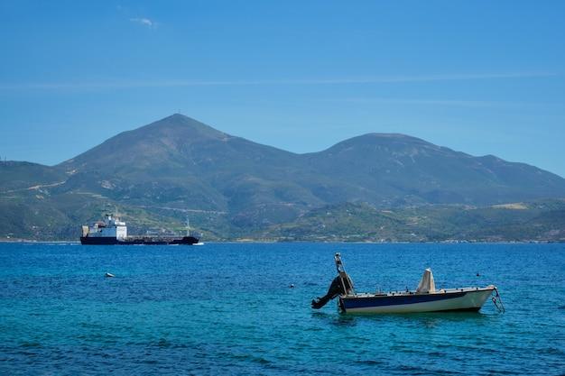 Griechisches fischerboot und frachtschiff in der ägäis griechenland