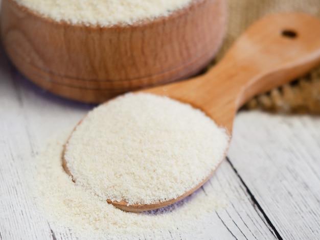 Grieß in einer holzschale und löffel auf einem weißen holztisch, nahaufnahme. gesunde ernährung getreide hintergrund.