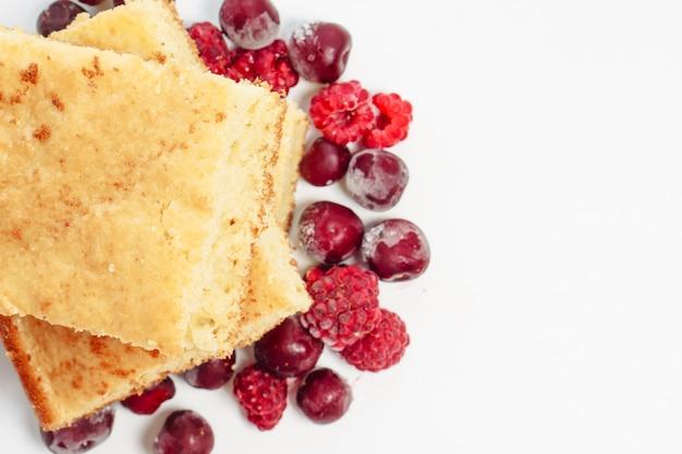 Grießkuchen mit himbeeren und kirschen isoliert auf weißer oberfläche