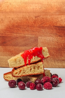 Grießkuchen mit himbeerkirschen und erdbeermarmelade auf einer holzoberfläche