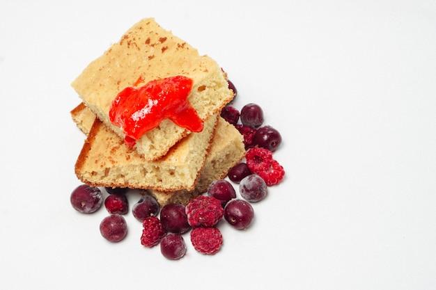 Grießkuchen mit himbeerkirschen und erdbeermarmelade isoliert