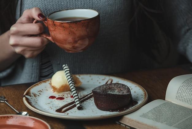 Gril, das einen tasse kaffee mit schokoladenfondue hält bild